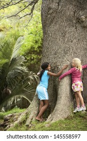 Full length of young girls hugging large tree