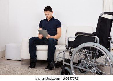 Full length of young handicapped man using digital tablet while sitting on sofa at home
