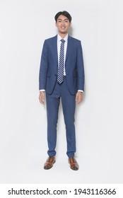 junger gut aussehender Geschäftsmann   Mann mit blauem Anzug mit weißem Hemd, Krawatte und blauer Hose, braune Schuhe