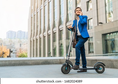 Full length of young handsome man in suit talking on phone while driving an electric scooter