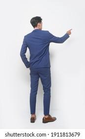 junger Mann mit einem blauen Anzug, Krawatte mit weißem Hemd und blauen Hosen, braune Schuhe, die mit dem Finger auf die Seite zeigen, im Studioaufnahme