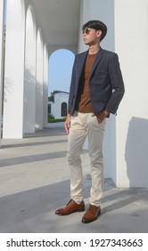 Volllange Junge gut aussehende Mann mit Brille, Anzug und zwangloser brauner Pullover Auf weißem Gebäude stehend