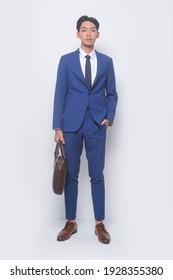 junge, gut aussehende junge Mann mit blauem Anzug, Krawatte mit weißem Hemd und blauer Hose, braune Schuhe, die die Hände halten Taschen, Handtaschen auf weißem Hintergrund,