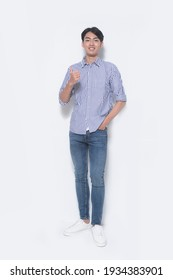 full length young handsome man wearing in striped shirt and blue jeans ,white shoes with hand, thumbs up  posing in studio