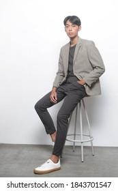 Junggut in voller Länge  Trageanzug, Hemd und Jeans mit weißem Sneaker, langStuhl auf grauem Hintergrund