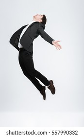 Full length young happy business man in black suit flying in studio isolated on a white background