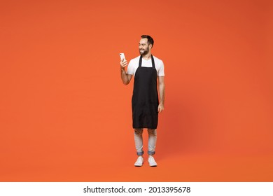 Full length young happy fun man barista bartender barman employee in black apron white t-shirt work in coffee shop using mobile cell phone isolated on orange background. Small business startup concept