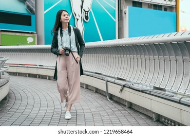full length young lady photographer relaxing walking on the bridge with camera. beautiful asian lady hobby taking picture from dslr camera. Japanese woman on holiday in city.