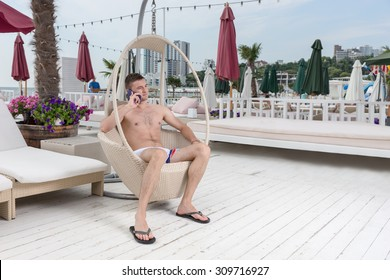 Full Length of Young Man in Bathing Suit Making Call on Cell Phone While Relaxing in Wicker Deck Chair on Patio of Oceanfront Luxury Vacation Resort