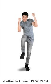 Full length of young man expressing happy while standing in the studio, isolated on white background