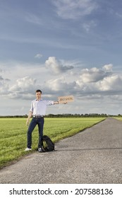 Full length of young man holding anywhere sign on empty road