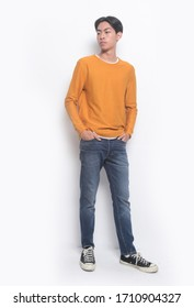 full length young man isolated on white background wearing brown shirts and blue jeans holding hands in pockets isolated over white background