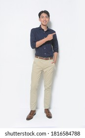 full length young man isolated wearing blue shirts and jeans khaki posing with brown shoes, fingers to the side