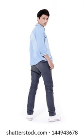 Full length young man in jeans standing back