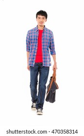 Full length young man in jeans with bag walking in studio