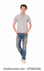 Full length young man in jeans standing with hands in pockets in studioi