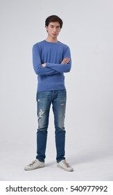 Full length young man in jeans standing with crossed arms