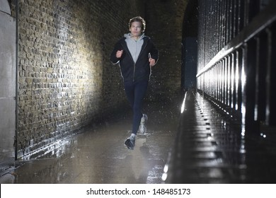 Full length of a young man jogging on street at night