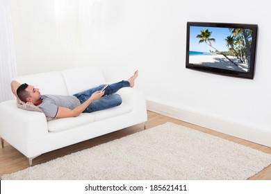 Full length of young man lying on sofa while watching TV at home