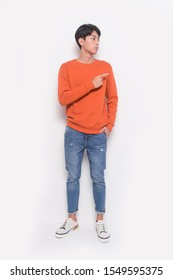 full length, young man in orange sweater with blue jeans standing with pointing with palm of hand