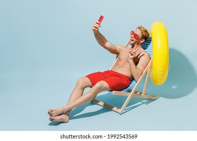 Full length young man in red shorts swimsuit glasses sit in chair inflatable ring do selfie shot mobile cell phone show v-sign isolated on pastel blue background Summer vacation sea sun tan concept - Shutterstock ID 1992543569