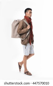 Full length Young man in shorts with big bag walking in studio