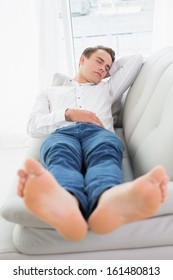 Full length of a young man sleeping on sofa in a bright house