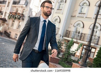 Full length of young man in full suit smiling while walking outdoors