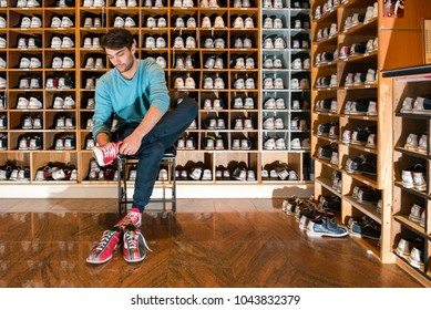 Full length of young man trying on bowling shoes in front of wooden selves at club