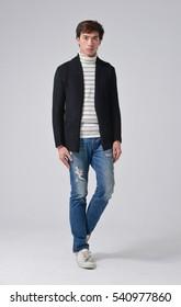 Full length young man walking in jeans walking in studio