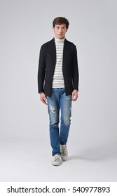 Full length young man walking in jeans walking â??gray background