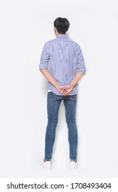 full length young man wearing jeans blue striped shirt with blue jeans-back view