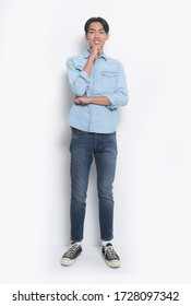 full length young man wearing jeans blue shirt with blue jeans with sneakers with hand on chin thinking