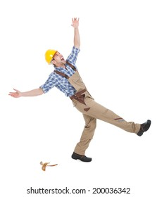Full length of young manual worker falling over white background