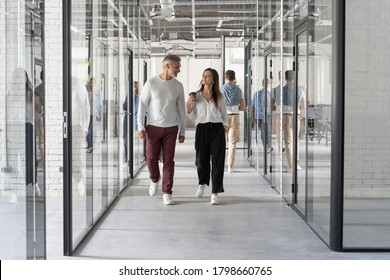 Full length of young modern people in smart casual wear having a discussion while walking through the office