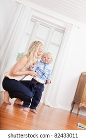 Full length of young mother and cute little child at home