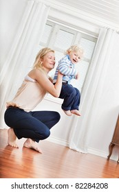 Full length of young mother playing with cute boy