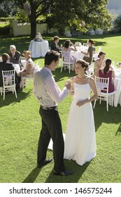 Full length of young newlywed couple toasting champagne while wedding guests sitting in garden