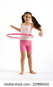 Full Length of Young Pretty Girl Playing Pink Hoola Hoop while Looking at the Camera. Isolated on White Background.