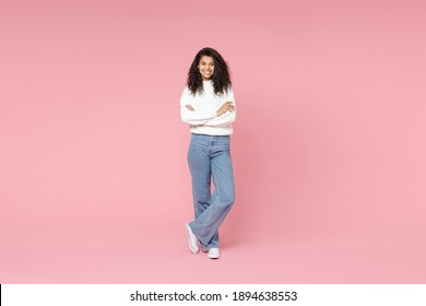 Full length young smiling african american woman 20s curly hair wear white casual knitted sweater jeans looking camera hold hands crossed folded isolated on pastel pink background studio portrait