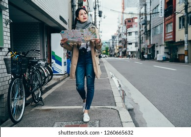 full length young tourist holding travel map in osaka city japan. Woman visiting sightseeing looking for directions at travel map on urban japanese street. female traveler walking by many bicycles.