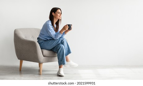 Full length of young woman drinking hot coffee in cozy armchair against white studio wall, banner design with free space. Peaceful lady having relaxing day, chilling on lazy morning - Shutterstock ID 2021599931