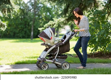 Full length of young woman looking into baby carriage in park