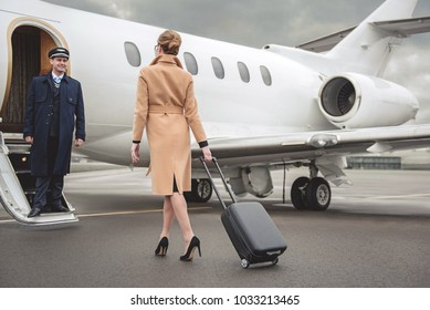 Full length young woman with luggage moving to plane. Outgoing aviator looking at her while sanding on entrance. Business concept
