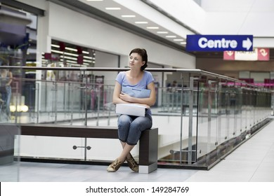 Full length of young woman with paper bag sitting in shopping centre