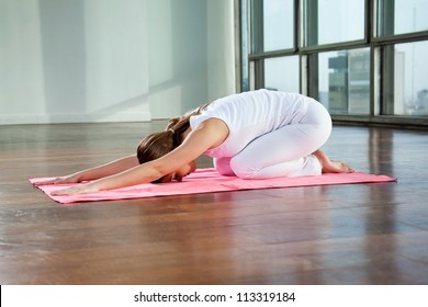 Full length of a young woman sitting in child's pose on a yoga mat