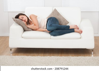 Full length of young woman sleeping on sofa at home