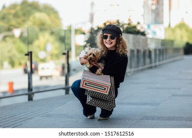 Full lenth of young woman with long curly hair holds small dog and shopping bags. Beautiful girl hugs little dog. Lady with puppy. Smiling attractive woman with Yorkshire terrier.