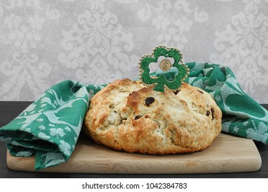 A full loaf of fresh baked Irish soda bread surrounded by a green shamrock towel.  Close up with copy space.