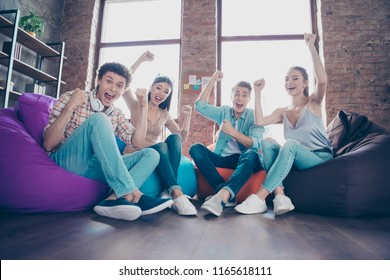 Full low angle view length, legs, body, size and dynamic image portrait of youth guys victoriously raising their fists up and rejoicing at the beginning of summer vacations low angle view